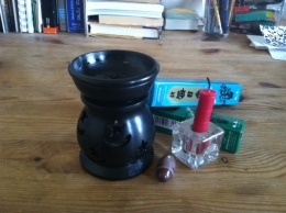 A black oil diffuser, a red candle, a small Shiva lingam stone, and two boxes of incense.