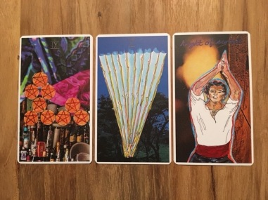 Image: 9 of pentacles, 10 of wands, and knight of swords. Further description in text.